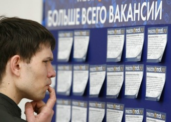 робота вакансия A man reads job offers posted at a job fair in Moscow